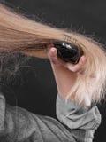 Blonde Frau, die ihr Haar kämmt Stockfoto