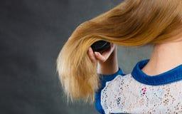 Blonde Frau, die ihr Haar kämmt Lizenzfreies Stockbild