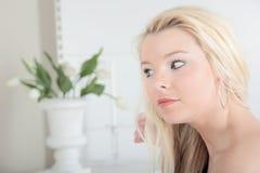 Blonde Frau, die ihr Haar pflegt Stockbild