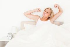Blonde Frau, die ihre Arme ausdehnt Stockfotografie