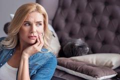 Blonde Frau, die ihre Kontrolle berührt und beiseite schaut Lizenzfreie Stockfotos
