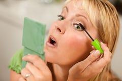 Blonde Frau, die ihre Wimperntusche anwendet Lizenzfreie Stockbilder