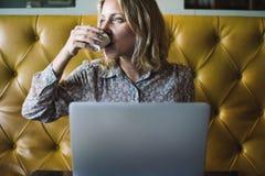Blonde Frau, die an ihrem Laptop an einem Café arbeitet Lizenzfreie Stockfotos