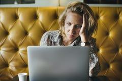 Blonde Frau, die an ihrem Laptop an einem Café arbeitet Lizenzfreies Stockfoto