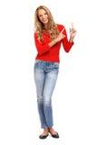 Blonde Frau, die ihren Finger in Richtung zum copyspace zeigt Stockfotos