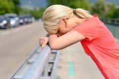 Blonde Frau, die ihren Kopf auf ihren Armen stillsteht Lizenzfreie Stockfotografie