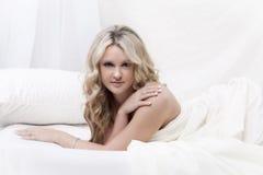 Blonde Frau, die im Bett liegt Stockbilder