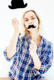 Blonde Frau, die im Bett mit gefälschtem Schnurrbart- und Papierhut sitzt Lizenzfreie Stockfotos