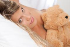 Blonde Frau, die im Bett mit Teddybären liegt Lizenzfreie Stockbilder