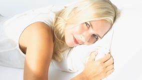 Blonde Frau, die im Bett und im Lächeln liegt Stockfotos