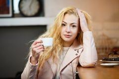Blonde Frau, die im Café stillsteht Lizenzfreies Stockbild