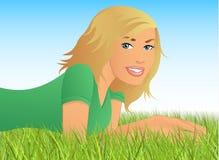 Blonde Frau, die im Gras liegt Lizenzfreies Stockbild