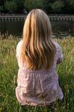 Blonde Frau, die im Gras sitzt Stockbild