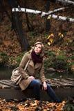 Blonde Frau, die im Herbstwald sich entspannt Stockfotografie