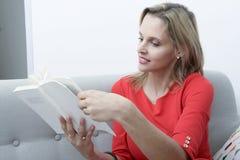 Blonde Frau, die im Sofa liest ein Buch sitzt Lizenzfreie Stockfotos