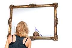 Blonde Frau, die im Spiegel schaut Lizenzfreie Stockfotos