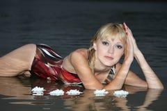 Blonde Frau, die im Wasser liegt Lizenzfreies Stockbild