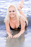 Blonde Frau, die im Wasser liegt Stockbild