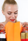 Blonde Frau, die Inhalt von farbigen Papiertüten kontrolliert Lizenzfreies Stockfoto