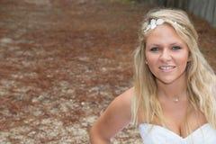 Blonde Frau, die Kamera betrachtend lächelt Stockfotografie