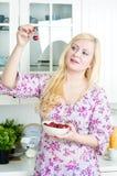 Blonde Frau, die Kirsche isst Stockbild