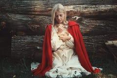 Blonde Frau, die kleines Kaninchen umarmt Lizenzfreies Stockbild