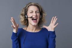 Blonde Frau, die am Kunden schielt und schreit Stockbild