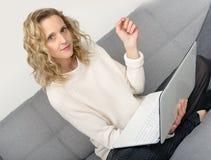 Blonde Frau, die Laptop auf dem Sofa verwendet Stockfoto