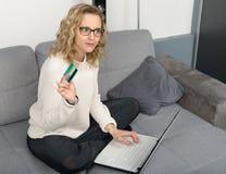 Blonde Frau, die Laptop für den Einkauf verwendet Stockfotografie
