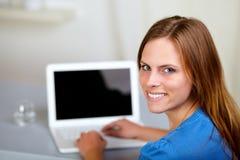 Blonde Frau, die an Laptop lächelt und arbeitet Stockbild