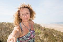 Blonde Frau, die man& x27 hält; s-Hand und Führung er auf Strand Stockbild