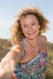 Blonde Frau, die man& x27 hält; s-Hand und Führung er auf Strand Lizenzfreie Stockfotos