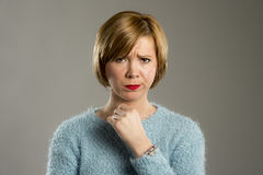Blonde Frau, die misstrauisch und im Unzufriedenheits- und Spannungsgesichtsausdruck mürrisch schaut Lizenzfreie Stockbilder