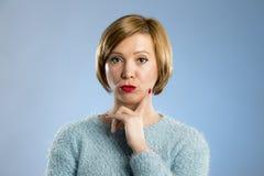 Blonde Frau, die misstrauisch und im Unzufriedenheits- und Spannungsgesichtsausdruck mürrisch schaut Lizenzfreies Stockbild