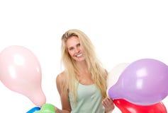 Blonde Frau, die mit Ballonen lächelt Stockbild