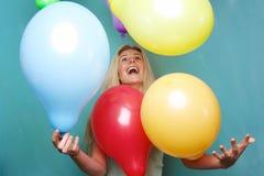 Blonde Frau, die mit Ballonen spielt Lizenzfreie Stockfotos