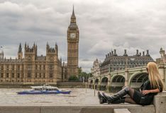 Blonde Frau, die mit Big Ben in London aufwirft Lizenzfreie Stockfotografie