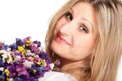 Blonde Frau, die mit Blumenstrauß sich dreht Stockfoto