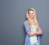 Blonde Frau, die mit den Armen gekreuzt lächelt Lizenzfreie Stockbilder