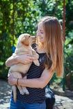 Blonde Frau, die mit einem weißen Labrador-Welpen spielt Lizenzfreie Stockfotografie