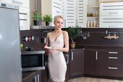 Blonde Frau, die mit einer Mikrowelle in der Küche kocht Stockfotografie