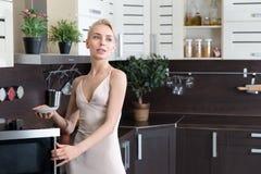 Blonde Frau, die mit einer Mikrowelle in der Küche kocht Stockbild