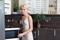 Blonde Frau, die mit einer Mikrowelle in der Küche kocht Lizenzfreies Stockfoto