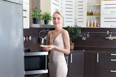 Blonde Frau, die mit einer Mikrowelle in der Küche kocht Lizenzfreie Stockfotos