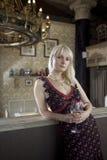 Blonde Frau, die mit Glas Wein in der Gaststätte steht Lizenzfreies Stockbild