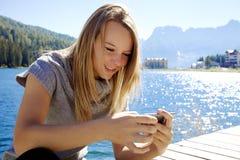 Blonde Frau, die mit Handy im Berg simst Stockfotografie