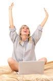 Blonde Frau, die mit Laptop auf Bett arbeitet Stockbild