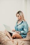 Blonde Frau, die mit Laptop auf Bett arbeitet Lizenzfreie Stockfotos