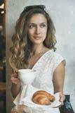 Blonde Frau, die mit Schale des Cappuccinos und des Hörnchens sitzt Lizenzfreies Stockbild