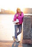Blonde Frau, die mit Schlittschuhen steht Lizenzfreie Stockbilder